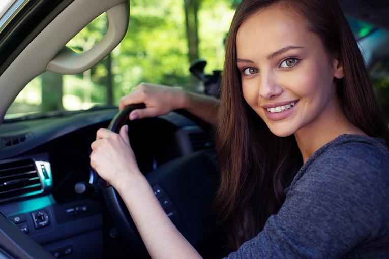 woman brown hair smiling holding car wheel