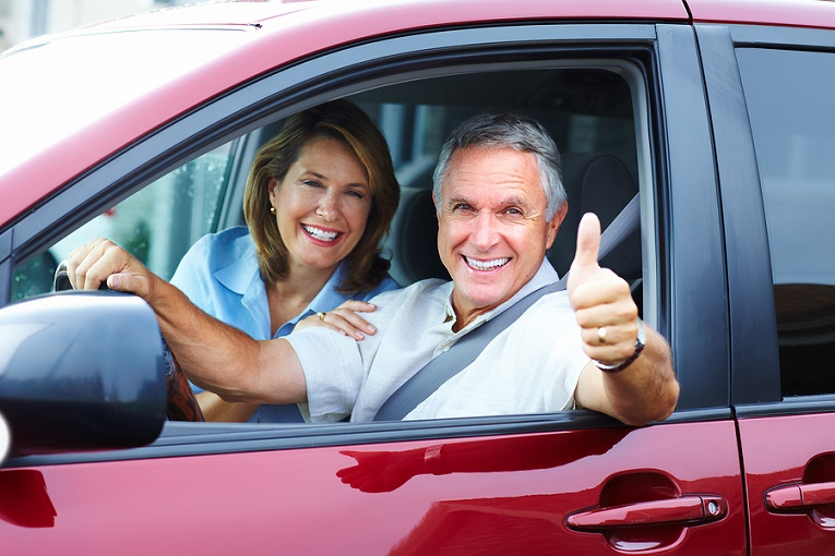 retired couple smiling in red van