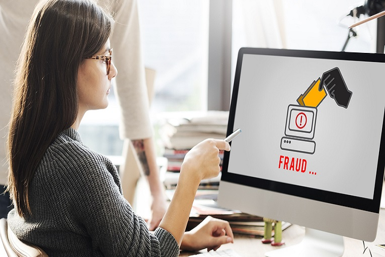 """""""woman looking at computer screen that says Fraud"""""""