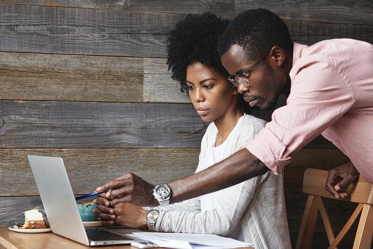 """""""man helping woman at laptop"""""""