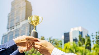 Businessman-Team-Holding-Award-367419283