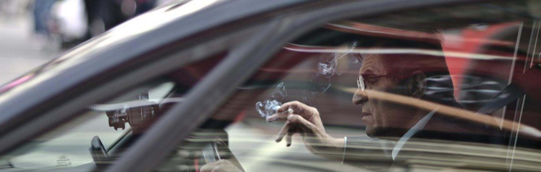 man with a cigarette driving a car